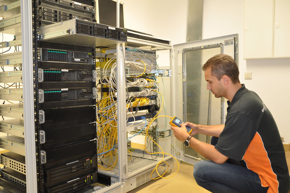 Techniker führt Messungen an Netzwerkschrank durch